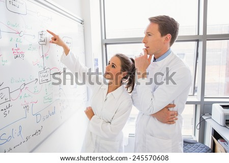 Science student and lecturer looking at whiteboard at the laboratory - stock photo