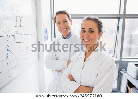 Science student and lecturer smiling at camera at the laboratory - stock photo