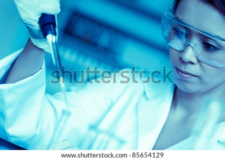 Science student dropping liquid in a test tube in a laboratory - stock photo
