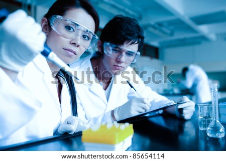 Science student dropping liquid in test tubes while her partner is taking notes in a laboratory - stock photo