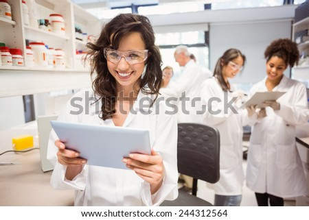 Science student holding tablet pc in lab at the university - stock photo