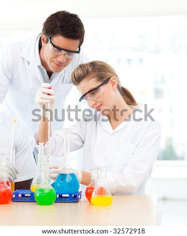 Science students examining test-tubes in a laboratory - stock photo