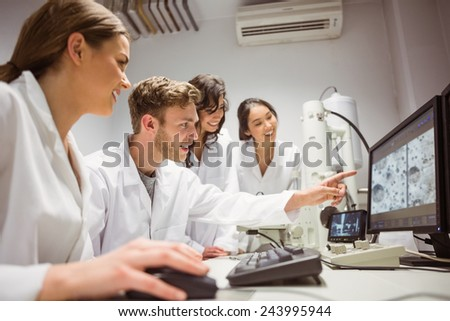 Science students looking at microscopic image on computer at the university - stock photo