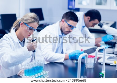 Science students working with chemicals in lab at the university - stock photo