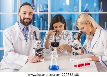 Science team working with microscopes in a laboratory. Smiling male science looking at camera. - stock photo