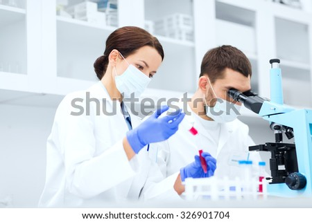 science, technology, biology and people concept - young scientists with pipette, test tube and microscope making research in clinical laboratory - stock photo