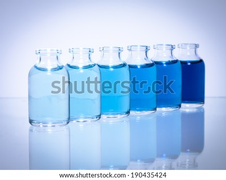 Science vials on a glass table with reflection in a diagonal line of transition blue colors on a white background with vignette.