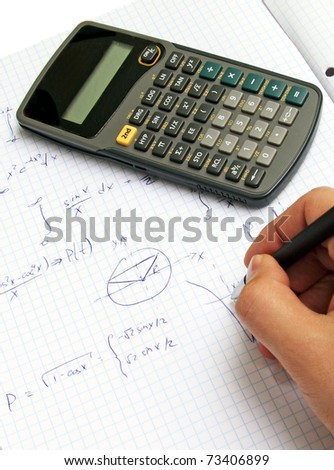 Scientific calculator on notebook paper - stock photo