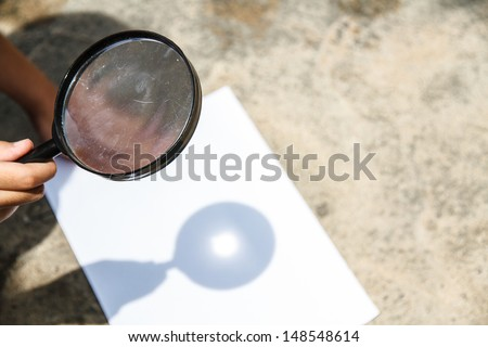 Scientific experiments. Use a magnifying glass to light the White Paper. - stock photo