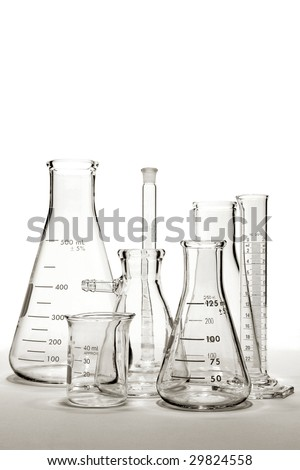 Scientific laboratory glass conical Erlenmeyer flasks with scientific cylinders and beakers assorted glassware for a chemistry experiment in a science research lab - stock photo