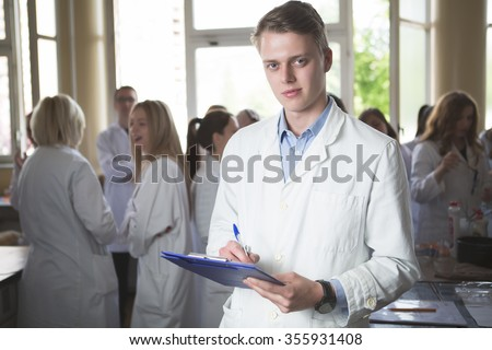 Scientific male researcher holding folder of chemical experiment research.Science students working with chemicals in the lab at the university.Happy student, content for experimental results.Pharmacy - stock photo