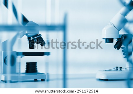 Scientific microscope lens on blue background, A microscope is an instrument used to see too small objects - stock photo