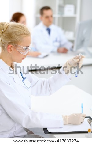 Scientific research team with clear solution in laboratory - stock photo