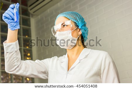 Scientific researcher holding at a liquid solution in the lab. - stock photo
