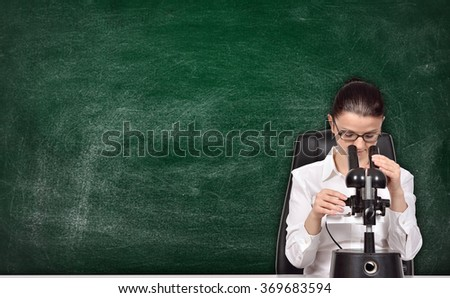 scientific researcher woman sitting in laboratory and studying the chemical sample - stock photo