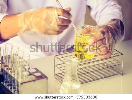 scientist are experimenting with yellow chemicals - stock photo