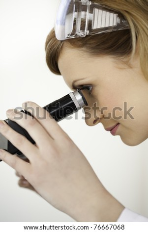 Scientist carrying out an experiment looking through a microscope in a lab - stock photo