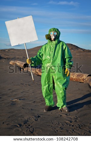 Scientist chemist with a placard in his hand in the area of chemical contamination - stock photo