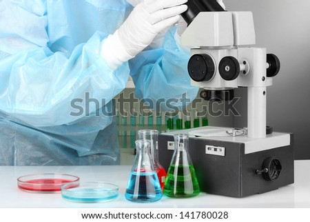 Scientist conducting research  looking through microscope selective focus close up - stock photo