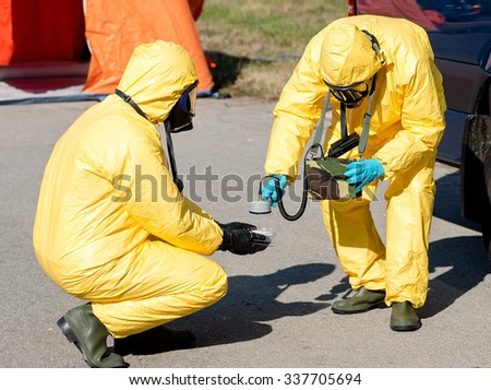 Scientist dosimetrist with radiometer and scientist radiation supervisor in protective clothing and gas masks examine a  sample of radioactive material in hazardous radioactive zone. - stock photo