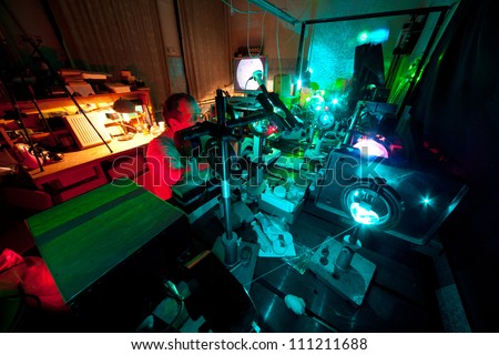 Scientist engaged in research in his lab about movement of microparticles by laser in dark lab - stock photo