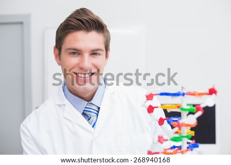 Scientist examining dna model and smiling at camera in laboratory - stock photo