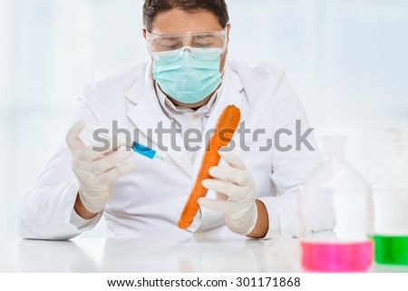 Scientist genetically modifying food. Carrot  - stock photo