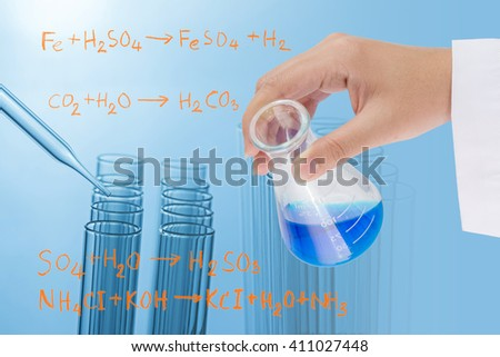 scientist hand holding flask with laboratory test tubes background - stock photo