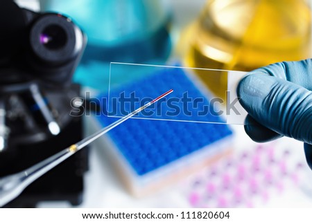scientist hand preparing slide for the the microscope - stock photo