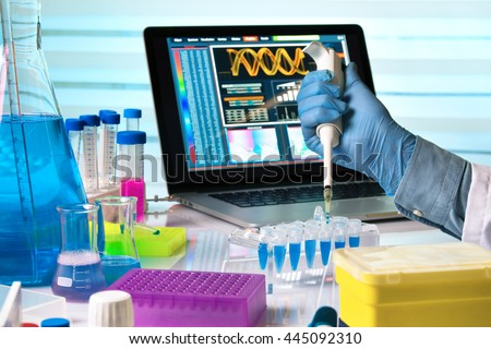 scientist holding dropper and working with laptop in genetics lab / researcher hands working with pipette and tubes in the laboratory table - stock photo