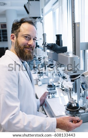 Scientist in laboratory looking through microscope
