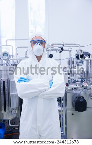 Scientist in protective suit standing with arms crossed in the factory - stock photo