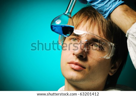 Scientist in protective wear and glasses looking at chemical flask - stock photo
