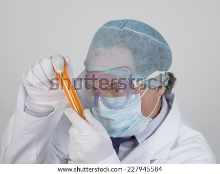 Scientist inspecting a test tube/Scientist and test tubes/Technician in protective gear inspecting lab apparatus  - stock photo