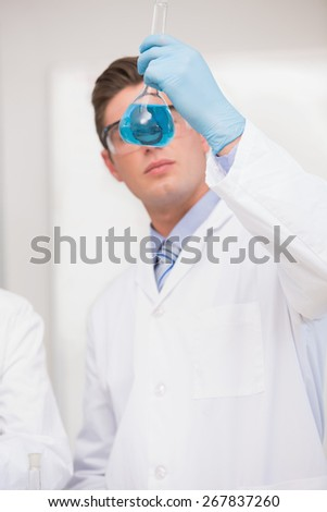 Scientist looking at beaker with blue fluid in laboratory - stock photo