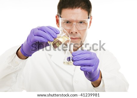 Scientist measures liquid as he pours it from a beaker to a flask.  Shallow depth of field with focus on liquid.