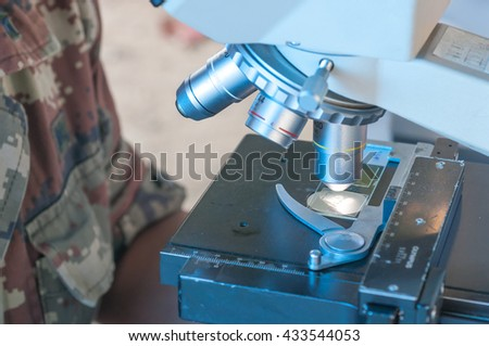 Scientist of Royal thai Army Medical  working with a microscope in laboratory