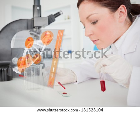 Scientist pouring drop of blood onto glass with futuristic interface in front of her - stock photo