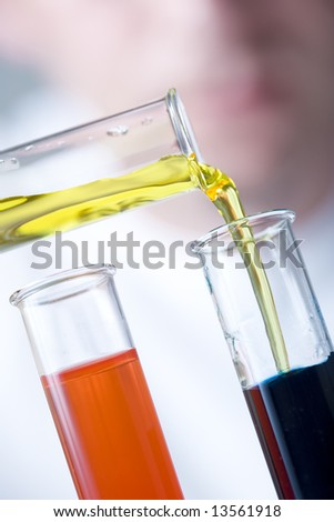 scientist pouring yellow liquid into test tube with dark blue liquid