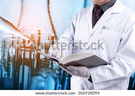 Scientist reading text book with test tubes background - stock photo