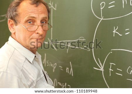 Scientist solves equation on blackboard - stock photo