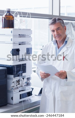 Scientist standing in lab coat holding a document in laboratory - stock photo