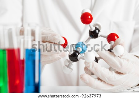 Scientist studying molecule model with test tubes in the foreground - stock photo