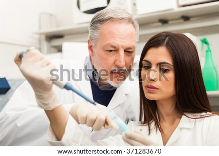 Scientist taking a sample from a test tube in a chemical laboratory. Shallow depth of field, focus on the woman - stock photo