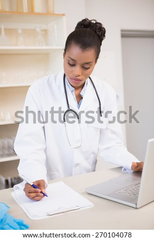 Scientist taking notes while using laptop in laboratory - stock photo