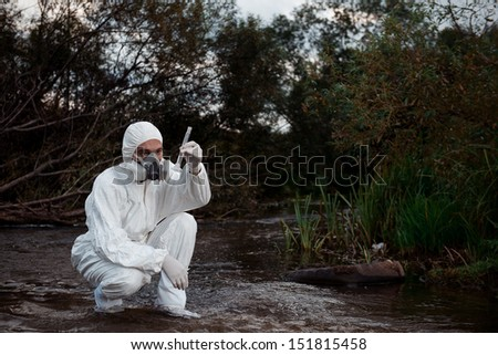 Scientist wearing a chemical protection suit takes a sample of contaminated water.  On a background of nature.