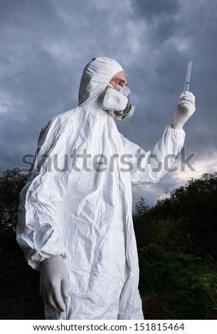 Scientist wearing a chemical protection suit takes a sample of contaminated water. On a background of sky. - stock photo