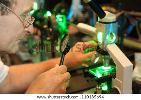 Scientist with glass, loupe configure  laser of microparticles - stock photo