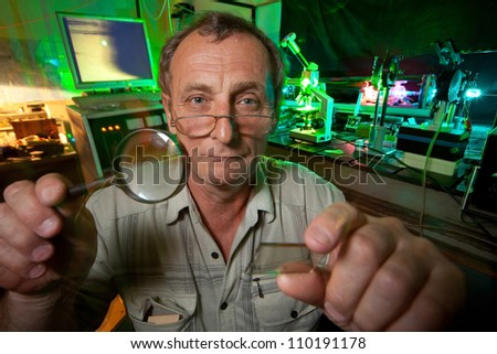Scientist with glass, loupe pose in his lab of movement of microparticles by laser - stock photo