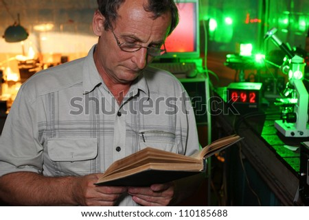 Scientist with glass read book in his lab of movement of microparticles by laser - stock photo